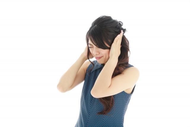 耳鳴りにより耳を防ぐ女性の写真